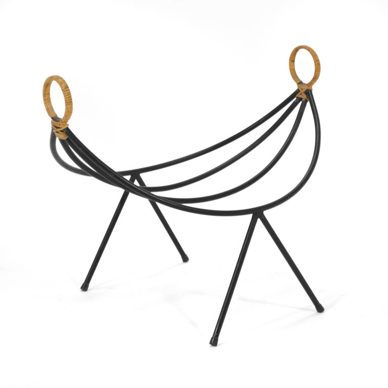 A brilliant design and a beautiful form, this iron stand with wicker wrapped handles keeps your magazines at hand or wood near the fireplace in sculptural style.