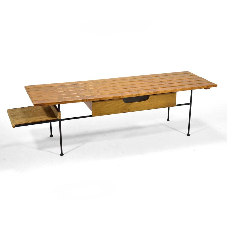 A terrific design by Arthur Umanoff, this table can also serve as a bench and utilizes Umanoff's signature modest materials: wrought iron, wood, and paperboard. The asymmetrical design features a slatted top, a pull-out drawer and a lower shelf, all