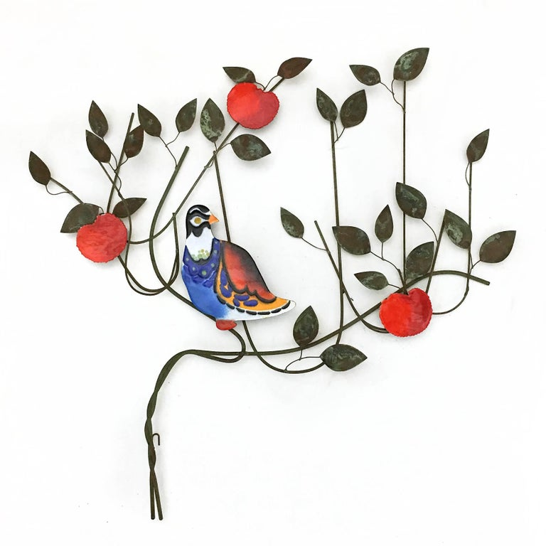 This uncommon Jeré wall sculpture from 1970 features a vividly colored bird resting in a fruit tree. It combines a wire composition of lyrical lines with patinated leaves and enameled elements.