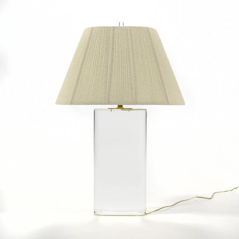 This spectacular table lamp has an oval base of three inch thick Lucite, the finest quality brass hardware, a perfectly matched shade of silky string and matching Lucite finial. The spare minimal form perfectly compliments the transparent material