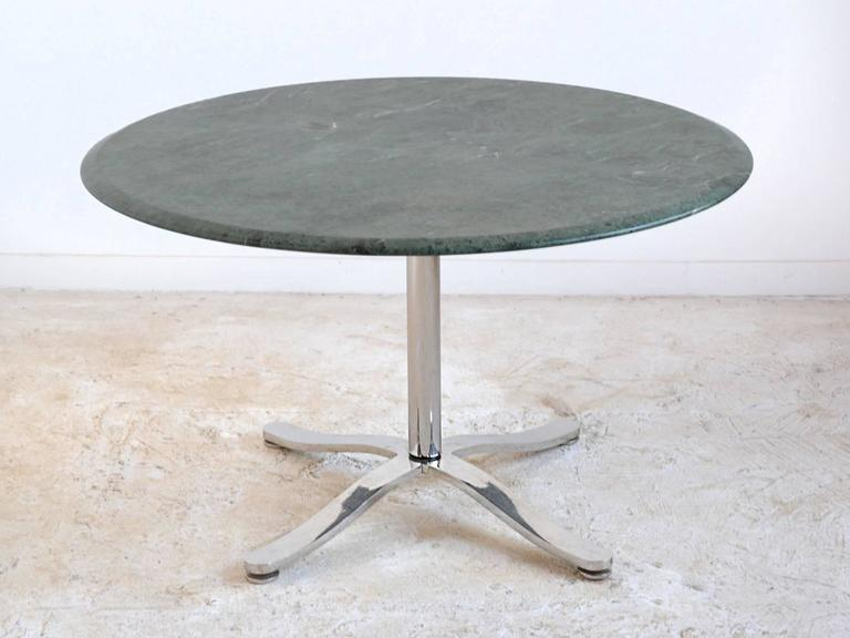 Zographos' aesthetic is one of quiet refinement, elegant lines, subtle details, and impeccable craftsmanship. This pedestal table designed in 1961 has a base of polished stainless steel and a emerald green marble top. Some of the delightful details
