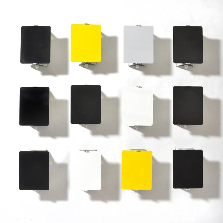 This spectacular set of 12 Perriand wall sconces is exceptional not only for the number of lamps, but the condition and the inclusion of three lamps in uncommon gray and yellow. A brilliant minimal design by Perriand, the pivoting shades shield
