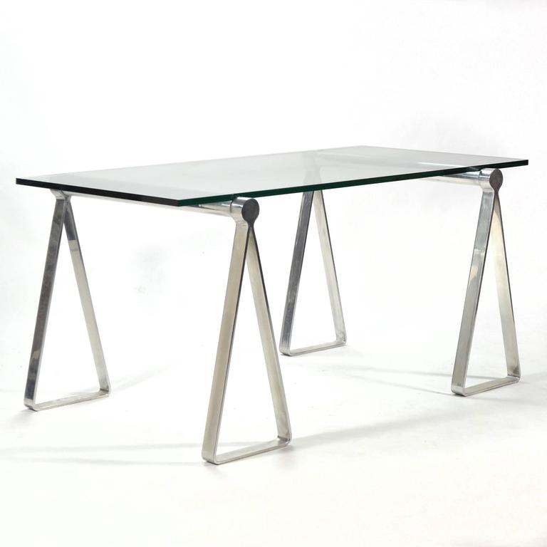 An ingenious and attractive design. Two Campaign-style aluminum sawhorse forms support a glass top creating a wonderful desk or table. The original glass shows damage–ordering a new glass top saves on shipping cost and allows you to select the