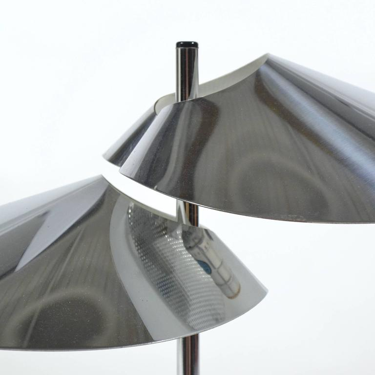 A subtle, elegant design by Jere, this table lamp has two heads of chromed steel which have been bent and folded into beautiful visor shapes. A perforated diffuser at the top of each allows heat to escape and prevents glare.