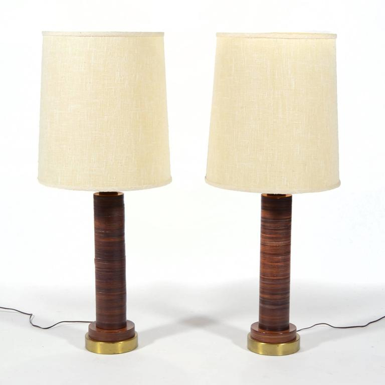 This handsome pair of table lamps have bases made of stacked leather. The leather imparts a richness and the striations add visual interest. The lamps have brass bases, brass hardware, and are topped with what appear to be the original ivory linen
