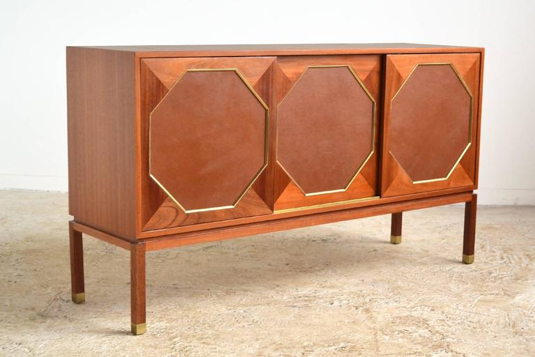 Harvey Probber's refined aesthetic shines in this three-door cabinet. Crafted of mahogany, it has three sliding doors with octagonal leather inserts framed in brass which conceal two compartments with two shallow slide-out drawers/ shelves and one