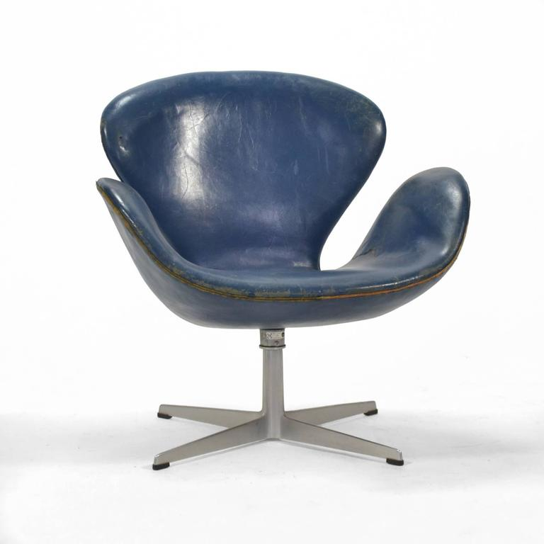 This early Jacobsen swan chair is for the collector who appreciates the original blue leather and the wear of a lifetime of use.