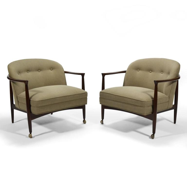 This design by finn Andersen features refined details and an exposed wood frame with lovely sculptural details supporting an upholstered seat. It references barrel-back club chairs and has casters under the front legs which is a detail that Edward