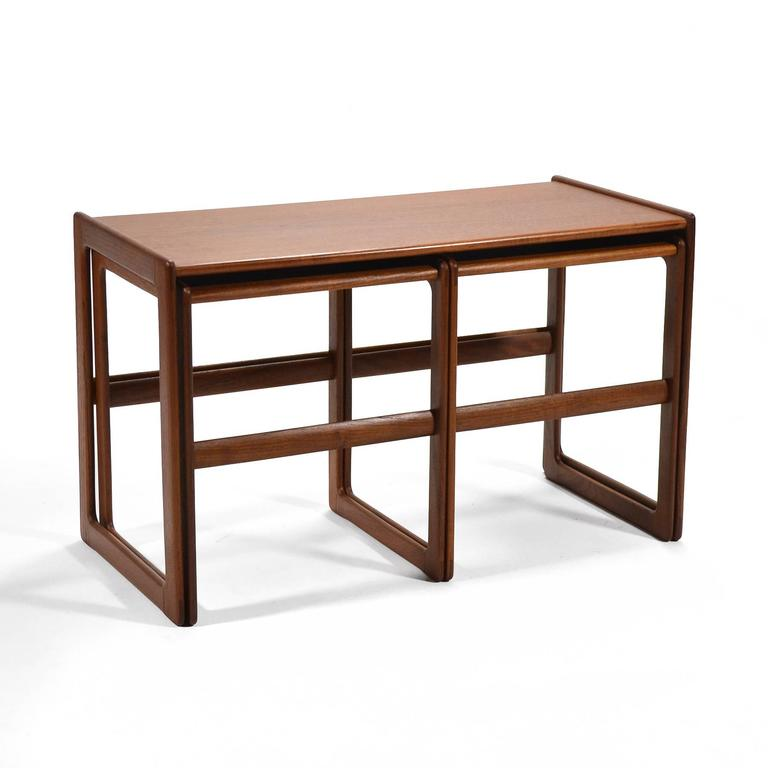 This lovely set of teak nesting tables in teak are not only handsome, they are incredibly versatile. The two smaller tables nest side-by-side under the larger table. With curved corners, raised edges, and exquisite joinery, they offer several