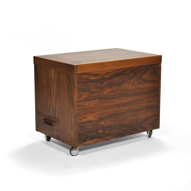 This delightful piece by Bruksbo serves double duty as a side table and a small portable bar. It has great presence with beautifully figured rosewood, nice brass hinges and exposed joinery. Opening it reveals a large storage compartment with a shelf