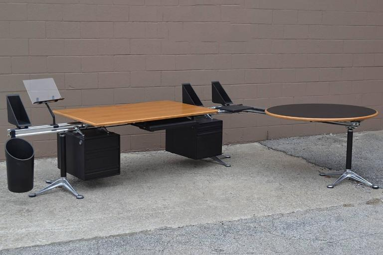 "This highly innovative design by Bruce Burdick uses an aluminium beam supported by legs with splayed cast aluminium feet to suspend all the necessary components to create what Burdick called ""workbenches for executives.""