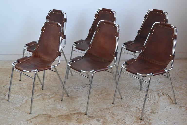 Specified for Charlotte Perriand's Les Arcs ski resort, these stacking chairs feature a chromed steel frame with a leather sling seat. The leather has acquired a beautiful patina from years of age and use.