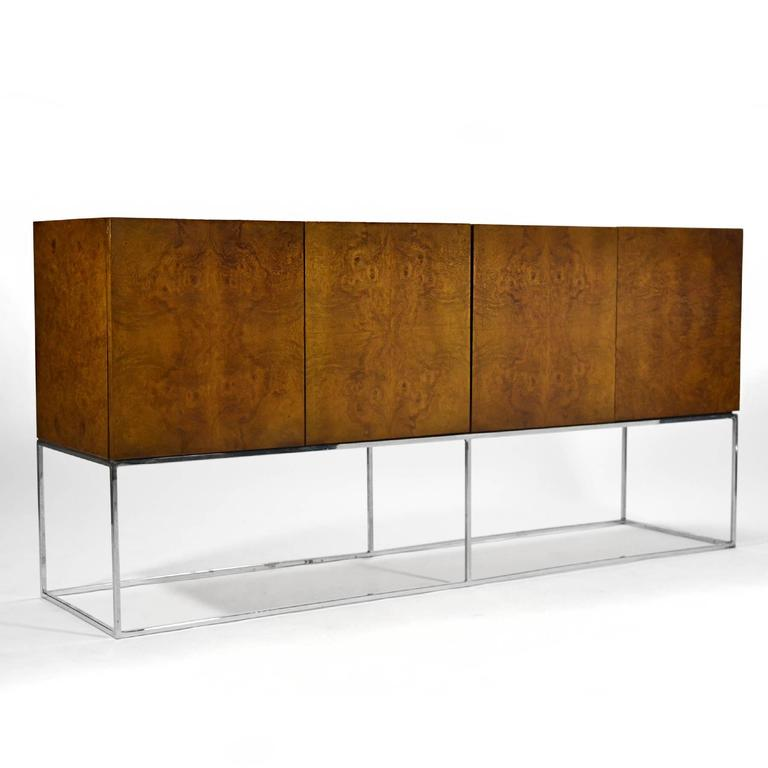 Perched on the chrome architectural base, this Milo Baughman credenza by Thayer Coggin has a great minimalist design paired with highly figured olive ash burl wood.
