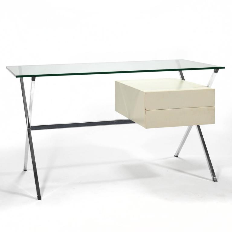 This beautiful minimalist desk was designed by Franco Albini in 1928. This example is a later edition by Knoll. It features a chromed X-form base supporting a glass top and an ivory lacquered oak two-drawer case.