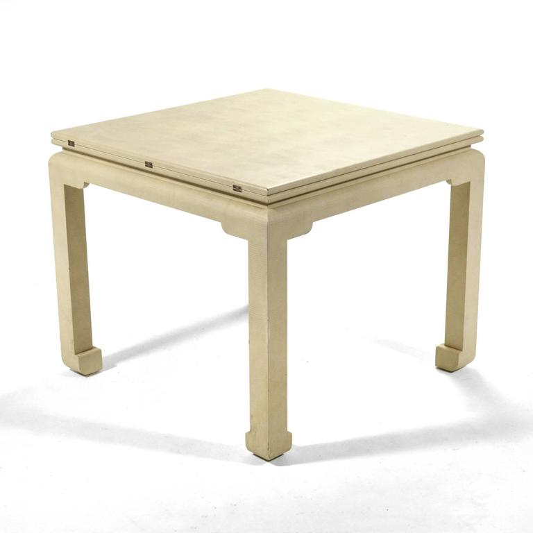 This striking game table by Karl Springer is clad in ivory snake-embossed leather and has a top that flips open to double in size allowing it to serve as a dining table.