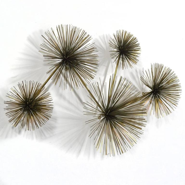 The Jere studio created a variety of designs using Bertoia's dandelion form as inspiration. This wall-mounted sculpture features a collection of five different sized bursts of radiating wire rods. A vibrant composition, it is equally attractive hung