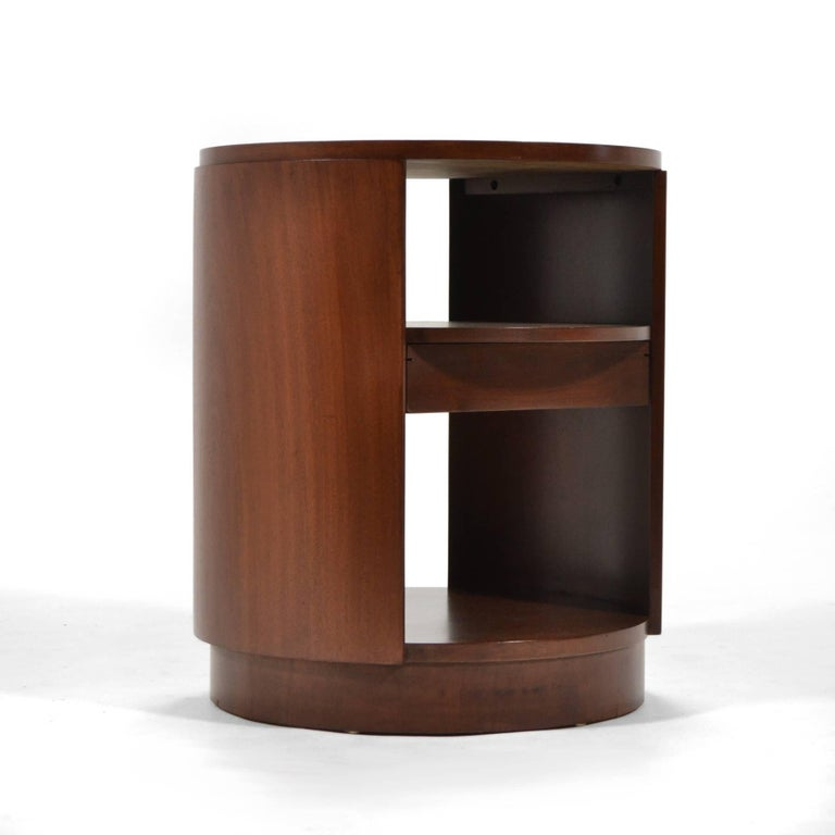 A beautiful design by Ed Wormley that references deco and modern aesthetics, this rare side table has a cylindrical form and a drawer below the middle shelf. Expertly crafted of mahogany by Dunbar and newly restored.