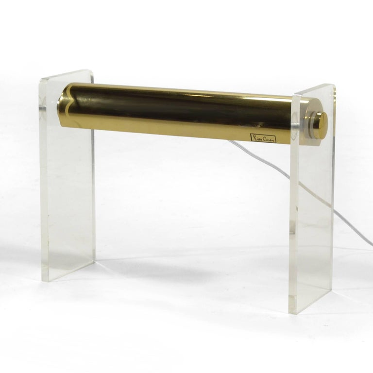 This elegant, minimal design utilizes two Lucite legs to support a pivoting brass shade.