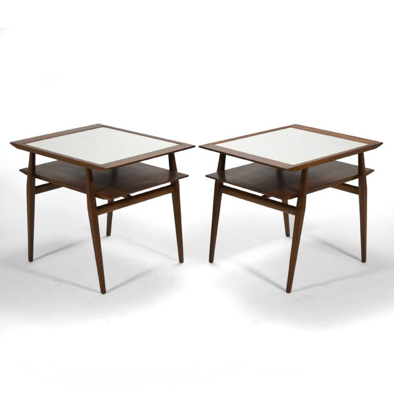 This handsome pair of Bertha Schaefer two tiered end tables in walnut have inset mica tops and dramatic angular lines. The design was designated model no. 2132 in the Singer and Sons catalog.
