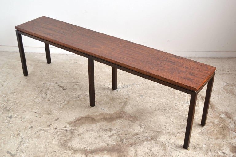A long, lovely sofa or console table by Harvey Probber with a top of rich rosewood supported by a dark mahogany base.