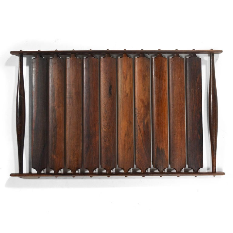 """This striking slatted tray by Jens Quistgaard is from Dansk's """"Rare Woods"""" collection. It is expertly crafted of rich, sold rosewood. There are ten slats with one flat side and one curved side, and two tapered handles on either end."""