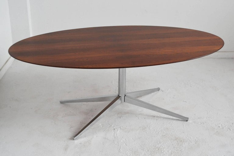 The beauty of the elegant form is equalled by the rich rosewood top of this table by Florence Knoll. It can serve as a dining table, conference table, or desk. Supported by an X-shaped pedestal base, the top is elliptical in shape and the underside