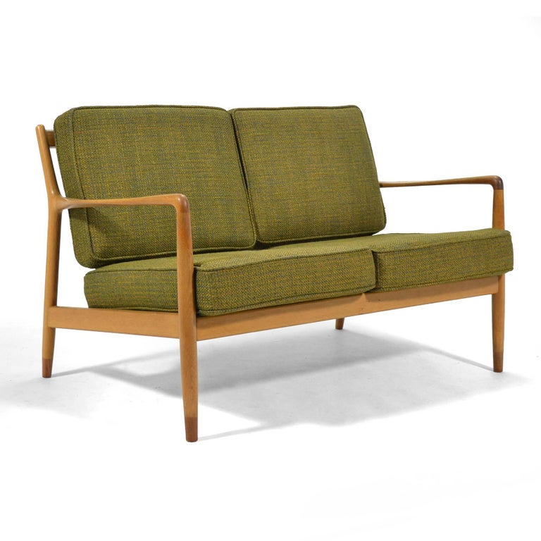 This beautiful early Folke Ohlsson two-seat sofa by DUX was crafted of solid oak with teak feet and an exquisite woven wool fabric. The original upholstery has been cleaned and restored with brand new foam.