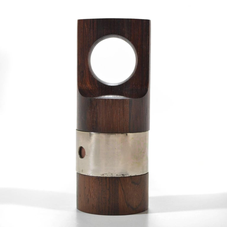 "Part of Dansk's ""Rare Woods"" collection this rosewood peppermil has a silver plated band with a hole to load the pepper corns and a Peugeot metal grinder. Combining qualities of sculpture and jewelry, it is the perfect exemplar of Quistgaard's"