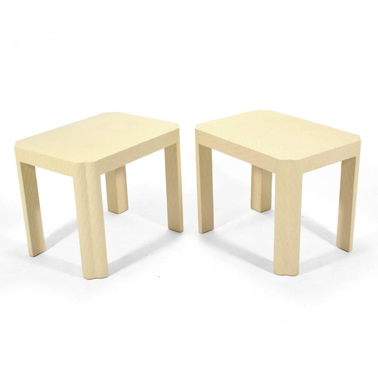 This pair of handsome side tables are very similar to the designs of Karl Springer. They are wrapped in a textured fabric, painted a warm ivory color, and have sculpted corners/ legs. Possibly made by Baker Furniture Co. they are unmarked.