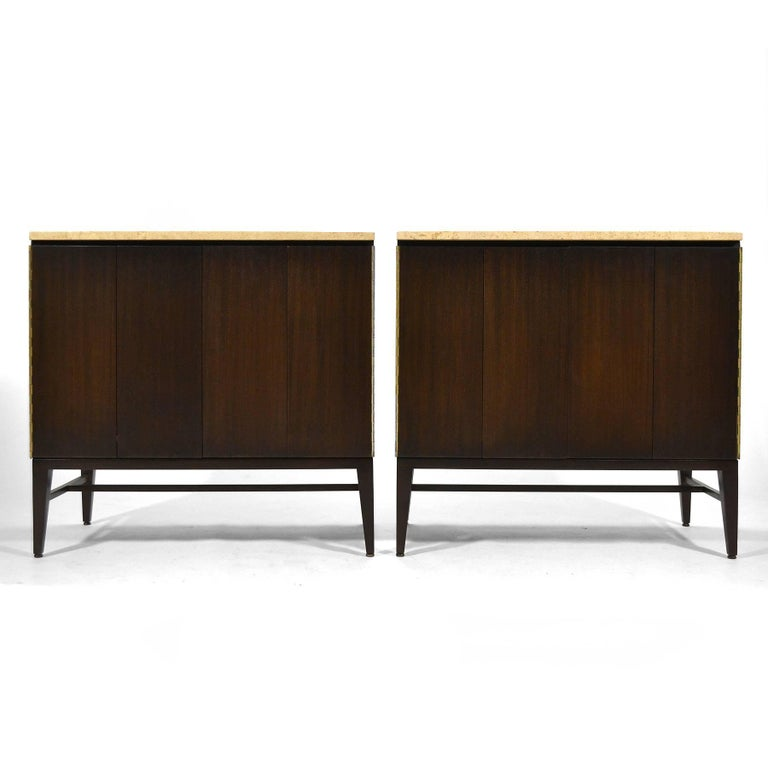 This pair of stunning McCobb cabinets by Calvin have a rich, dark finish on the mahogany cases and are topped with Italian travertine. One is fitted with four drawers, the other a single adjustable shelf. They were used by the original owner as a