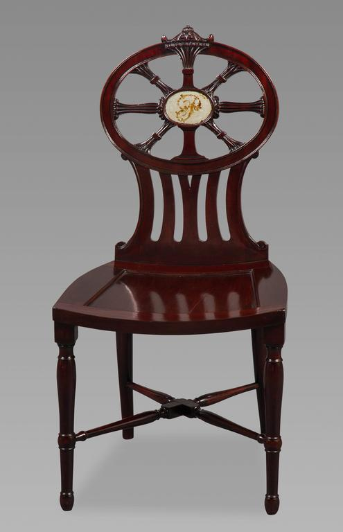 The four chairs of the finest quality mahogany, the backs with an oval six spoked compass design centered by an oval plaque painted with a floral