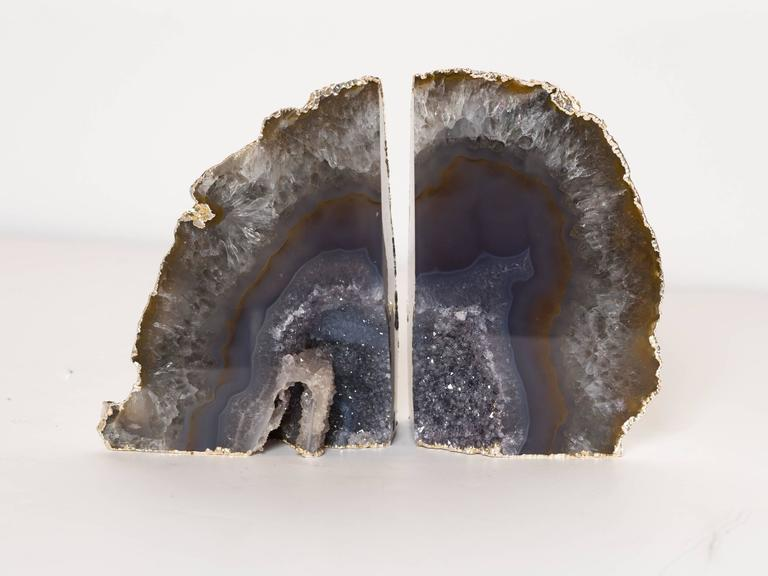 Stunning pair of natural agate stone bookends with fine amethyst crystalline centers. Organic stone with polished fronts with natural rough edges that have been finished in 24-karat white gold electroplating. Can be used in different configurations