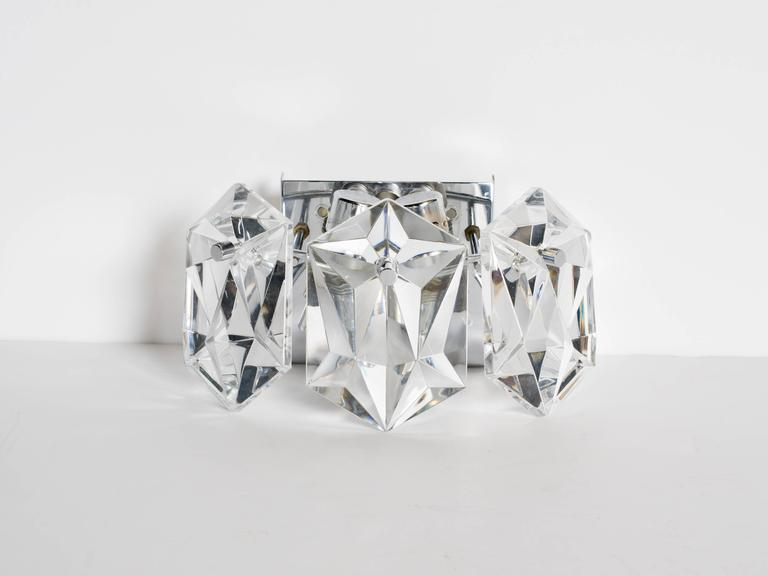 Exquisite mid-century modern wall lights, fitted with three faceted crystal prisms. Simple floating frames are finished in polished nickel with matching fittings. Newly rewired and fitted with two lights each. Perfect scale for powder room, vanity,