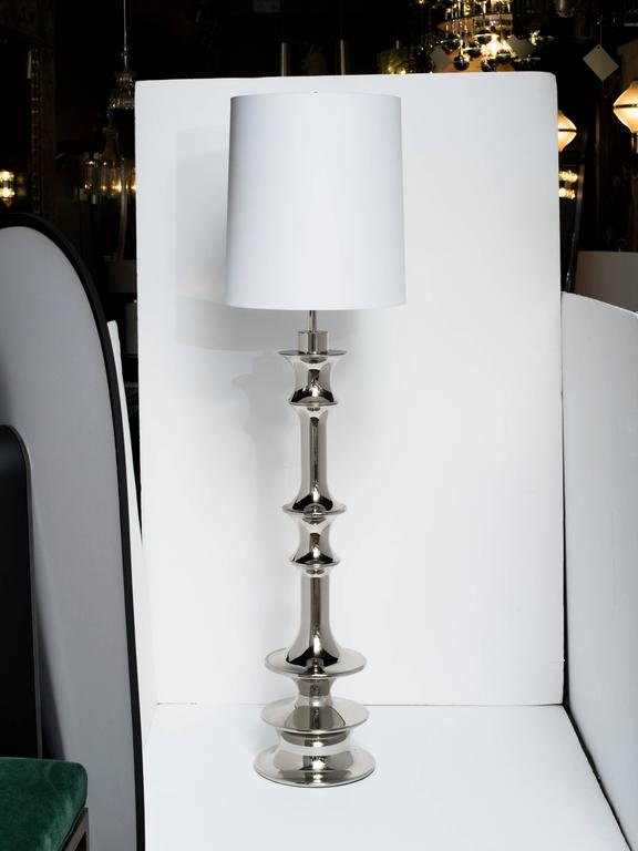 Pair of tall dramatic Hollywood Regency floor lamps with architectural design. Lamps feature highly stylized baluster forms in polished nickel finish. The sculptural design is reminiscent of Queen chess pieces.  Shown with drum shades in white.