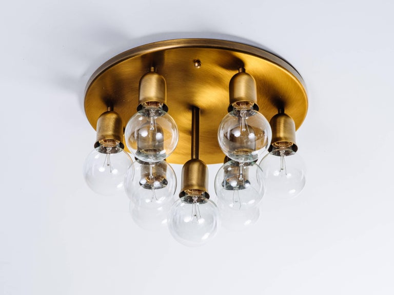 Mid-Century Modern round ceiling light or wall sconce, with sculptural Sputnik design. Fixture has a dark brass or brushed bronze metal finish, and is fitted with ten lights. Light sockets hang at varying heights to create atomic form.