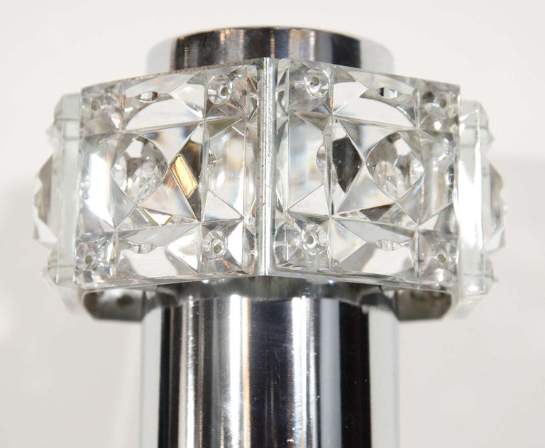Gorgeous Austrian Mid-Century Modern sconce with barbell form. The sconce has a chrome frame with cut crystal faceted glass details. The sconce is fitted with two lights, one uplight and one downlight. While illuminated the sconce also casts light