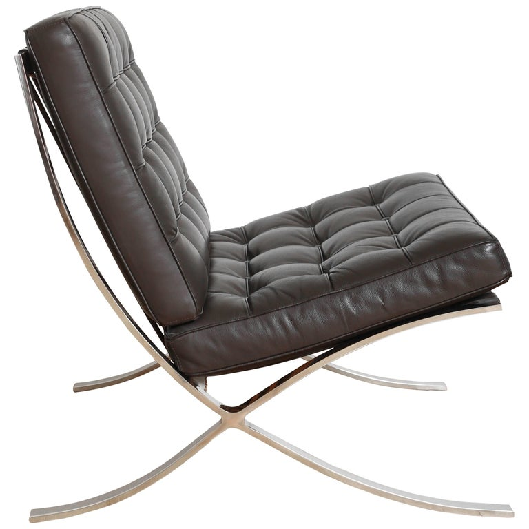 Vintage Barcelona lounge chair in espresso brown leather. Iconic design originally manufactured during the Bauhaus Movement, circa 1929. The chair has a slight recline, and features leather slats along the back with tufted seat cushions. Suited for