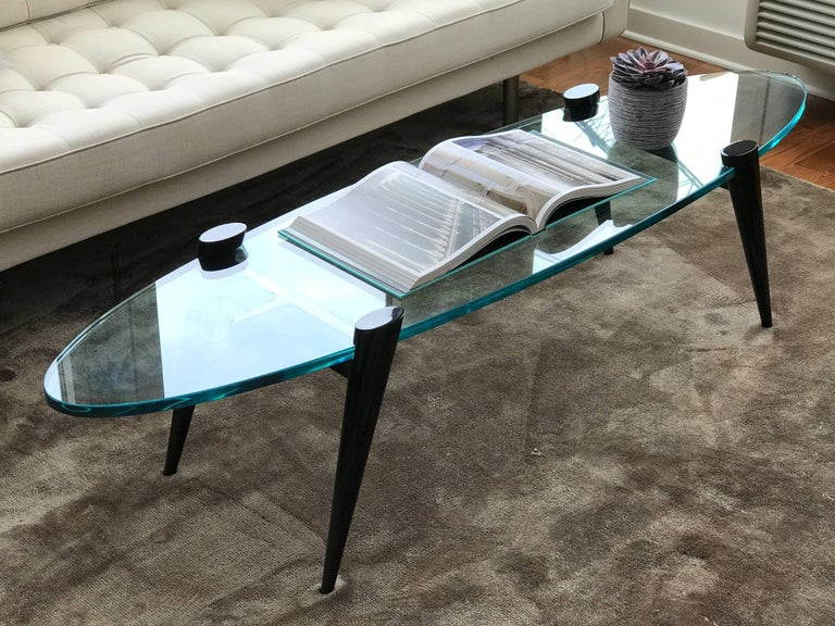 Mid-Century Modern cocktail table with elegant tapered leg design. Legs function as table bases in ebonized walnut wood. Fitted with thick hand beveled elliptical or surfboard glass top. Ultra modern design great looking from all angles.