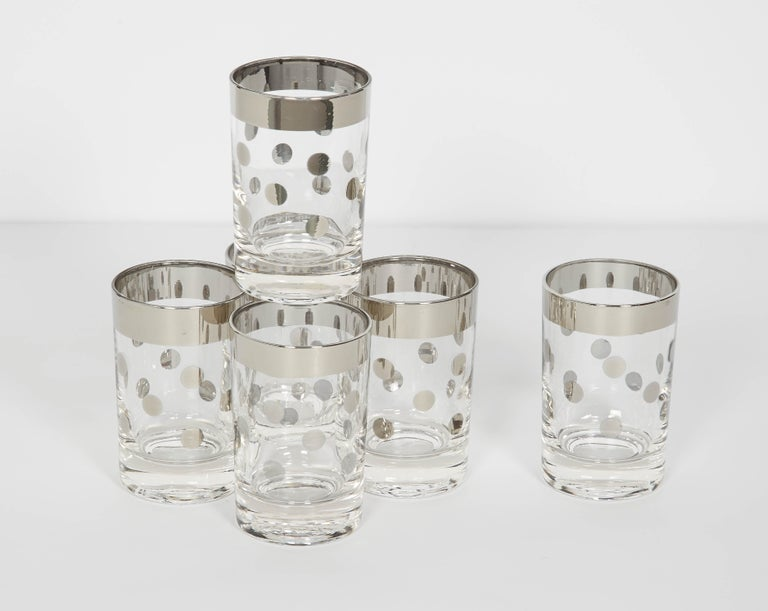 Mid-Century Modern barware glasses consisting of six perfect cylinder small cordial glasses or liqueur glasses. The glasses have a chic silvered metal trim with polka dot design. Makes a smart and cheerful addition to any barware set or serving set.