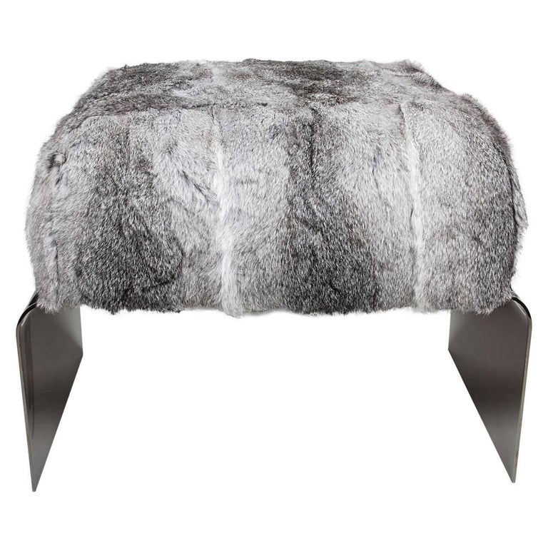 Stunning Mid-Century Modern style stool with streamlined waterfall base design in polished black nickel. The bench is upholstered in luxurious rabbit fur invariant hues of grey. Great accent piece for any room and also great as an ottoman.