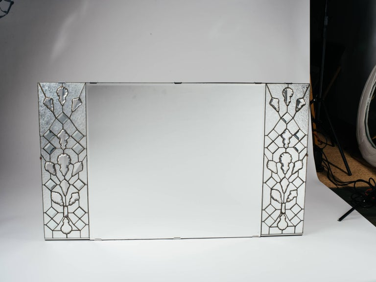 Exquisite and opulent Mid-Century Modern rectangular mirror with Hollywood Regency design. Features transparent stained glass panels on either side, and fitted with stunning large cut crystals.