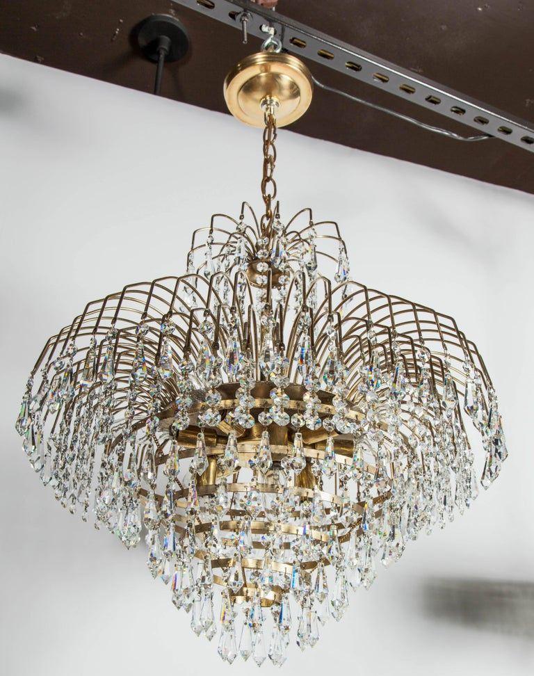 Mid-Century Modern waterfall chandelier with spectacular cut crystals throughout. Features a brass frame with multiple cascading tiers, fitted with hundreds of suspended cut crystal pendants and crystal beads. The frame is comprised of ten-tier in