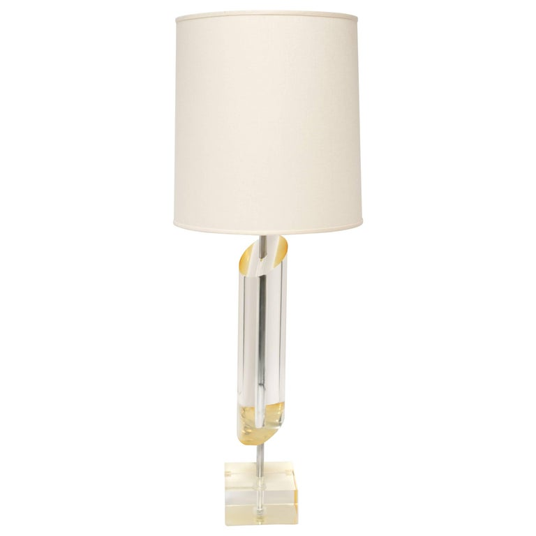Sculptural Mid-Century Modern lamp with slanted column design. Lamp is comprised of solid Lucite cylinder with asymmetrical design and heavyset Lucite base. Lucite has amber or golden undertones and is fitted with two lights, featuring on/off chain