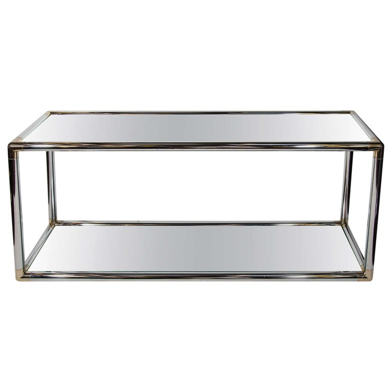 Italian Mid-Century Modern console table or sofa table with two-tier design. Comprised of tubular chrome frame with rounded brass corners, and fitted with mirrored tops. In the style of Romeo Rega.