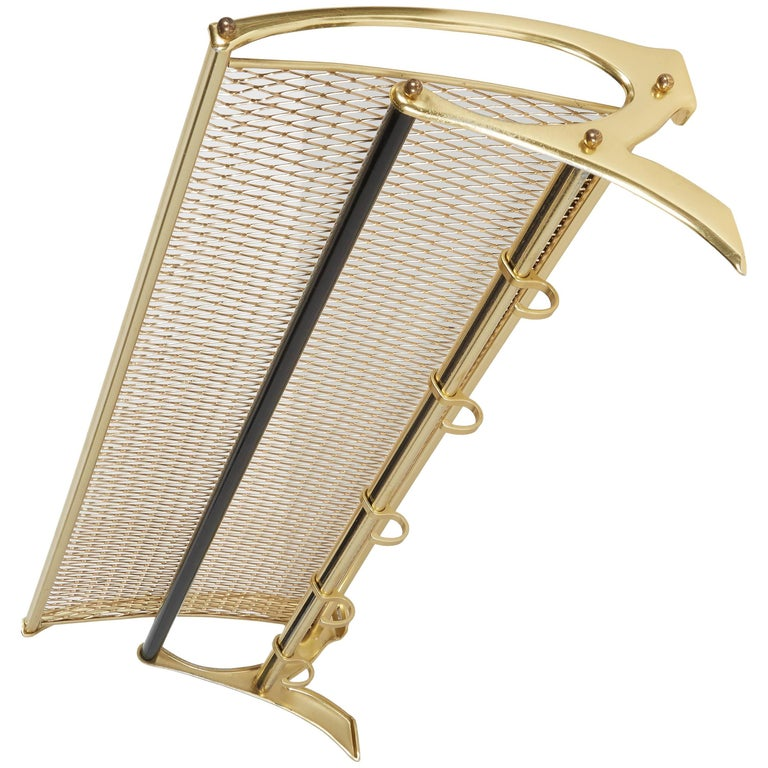 Austrian Mid-Century modern coat and hat rack with wall mount design. Brass-plated metal with modernist design includes gold metal grid top shelf and cross bars with black enameled details. Fitted with five sliding coat or jacket hooks. Great