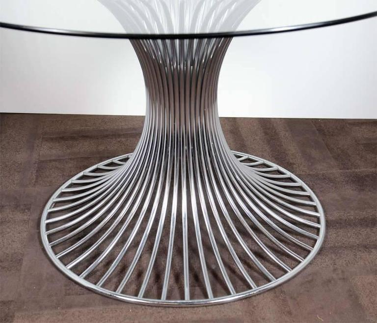 Outstanding Mid-Century dining table has a sculpted tubular chrome base and features a round glass top. Distinguished tulip table design, exemplary of architectural designs of the 1960s and in the style of Warren Platner.