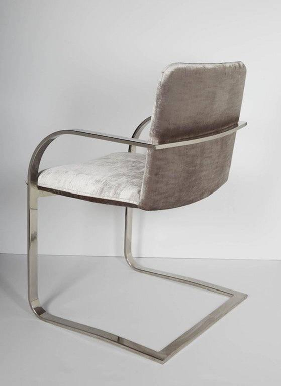 Mid-Century modern desk chair with cantilevered frame design. Chair has streamlined profile with curved armrests and floating seat details. The chair is made of a polished steel frame. Newly upholstered in luxe platinum velvet-cotton fabric.