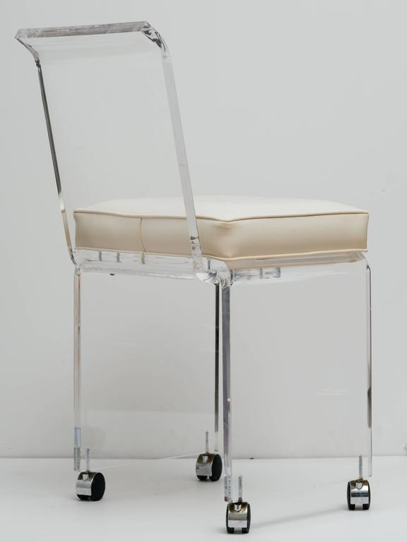 Mid century modern lucite vanity chair with full back design. The vanity stool has a sleek streamline design with polished beveled edges. Features swivel casters for effortless movement. Shown with original white naugahyde seat. Price includes