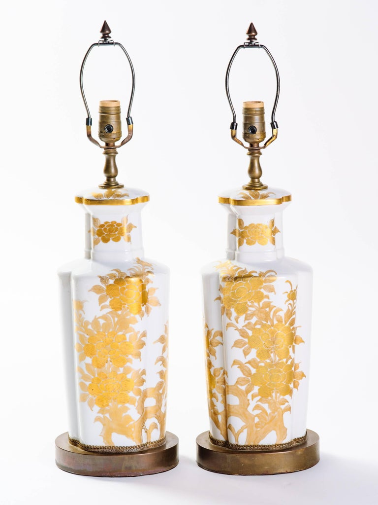 Pair of elegant Japanese porcelain lamps with hand-painted floral motif. Mid-Century lamps have white glaze finish with gold leaf designs, and hand-forged bronze base and fittings. Shown with custom narrow drum shade in silk.