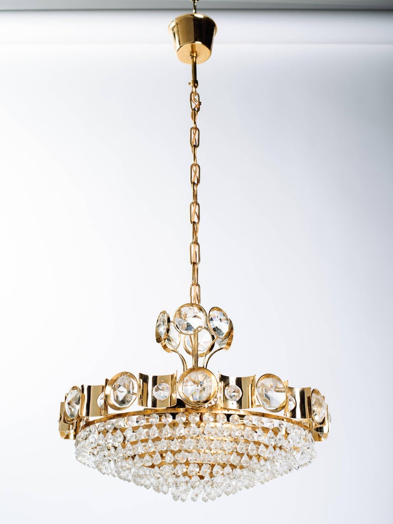Exquisite Hollywood Regency style chandelier with gold-plated over brass frame. The chandelier has a circular multi-tiered design with scalloped details. Fitted with rows of cut crystals and stunning oversized jeweled crystals along the top.